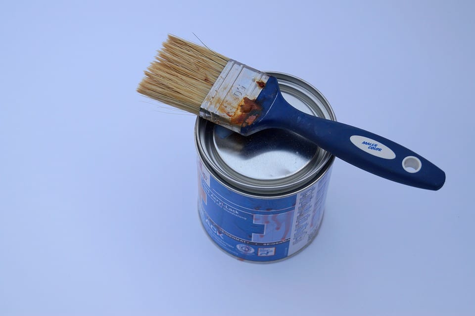 A clean paintbrush sitting on a closed can of paint