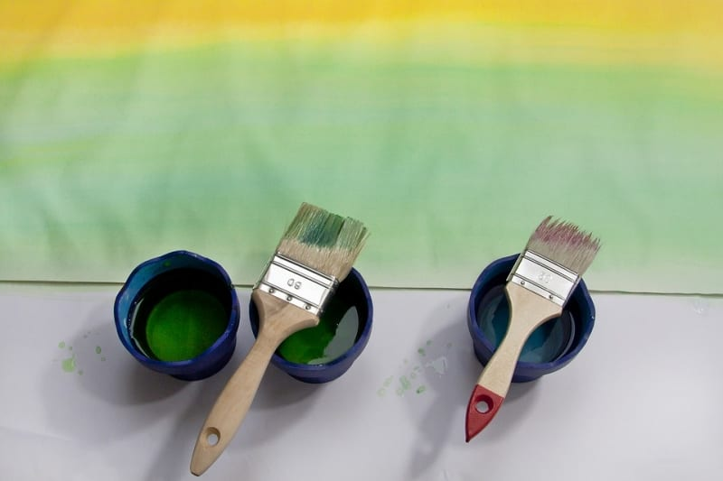 Two paintbrushes sitting on containers with paint in them
