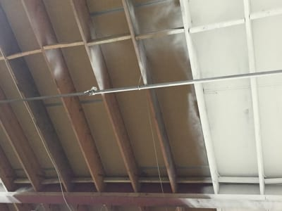 Interior ceiling of a garage being painted in process