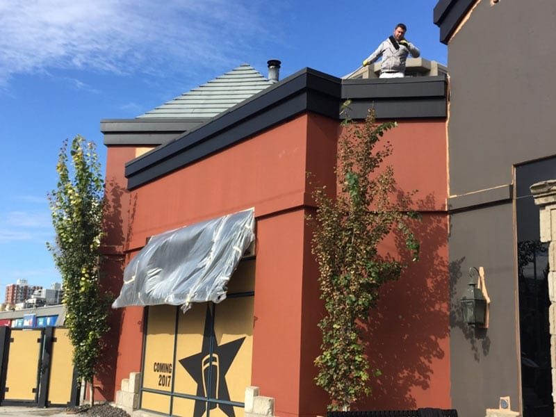 A worker paints the exterior of a restaurant