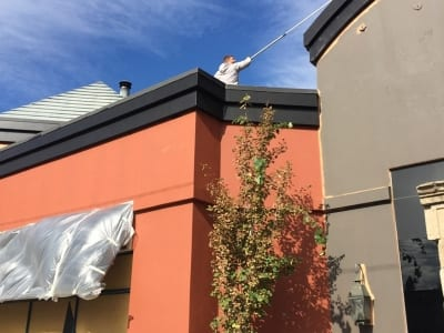 A worker paints the exterior of a restaurant - standing on roof