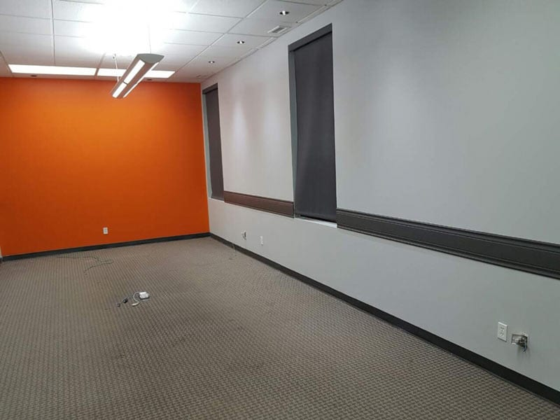 Recently painted interior of an office space with one accent orange wall