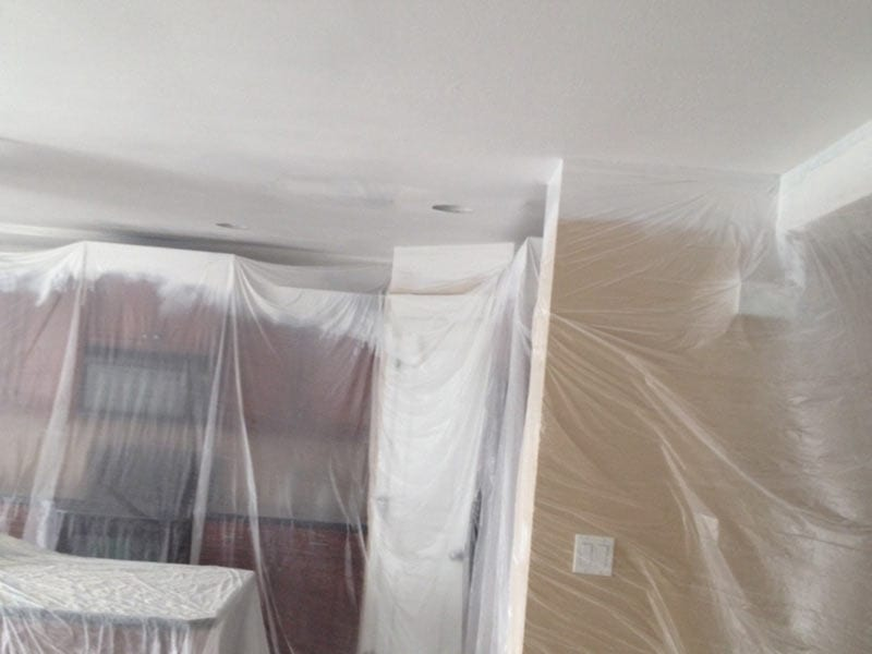 A home being prepared for painting with copious amounts of plastic film in Kitchen